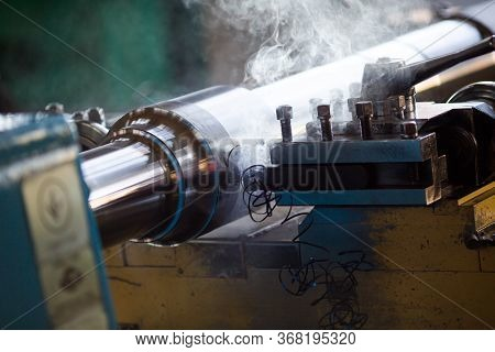 Close-up. A Milling Machine Cuts A Metal Part. Steaming Steel Part On The Machine.