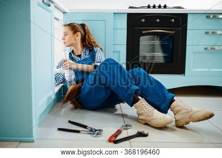 Cute female plumber in uniform holds drain pipe