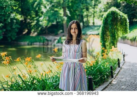 Sofia Park, Uman. Beautiful Girl With A Tourist Map Walks In The Summer Park. The Girl In A Dress Wa