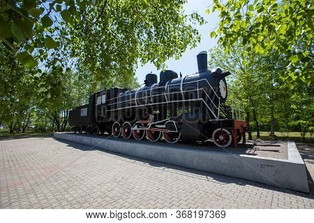 An Old Steam Locomotive Of Black Color Stands On A Pedestal In A Park On A Background Of Green Trees