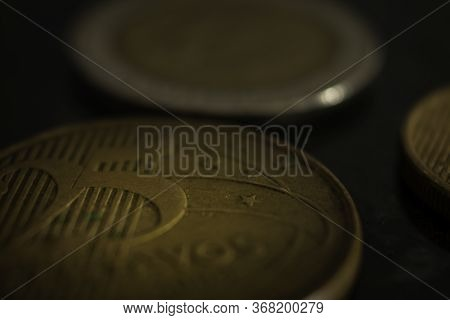 Close Up On Two Coins On A Black Table. Selective Focus. Capitalism Concept.