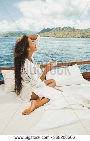 Woman Enjoying Morning Coffee On Boat In Private Cruise Tour. Bed On Board. Travel And Freedom Lifes