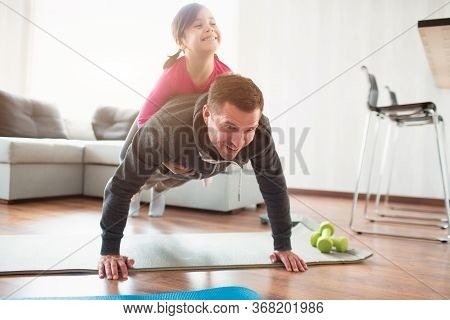 Father And Daughter Are Training At Home. Workout In The Apartment. Sports In Home Conditions. They