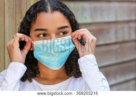 Mixed race teenager teen girl young woman wearing fitting and adjusting a face mask during the Coronavirus COVID-19 pandemic