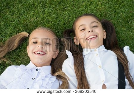 Happy Childhood Experience. Happy Children Relax On Green Grass. Enjoying Childhood Years. Childhood