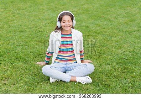 Do Not Bother Me. Listen Music While Relaxing Outdoor. Kid Girl Enjoy Music Green Grass Meadow. Plea