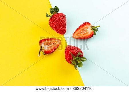 A Top View Strawberries Sliced Whole Juicy Mellow On The Yellow Blue Desk