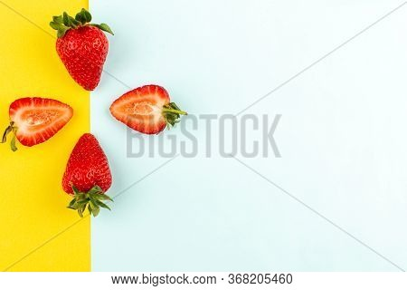 A Top View Red Strawberries Juicy Mellow On The Blue Yellow Background