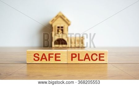 Wooden Blocks Form The Words 'safe Place' Near Miniature House. Wooden Table. Beautiful White Backgr