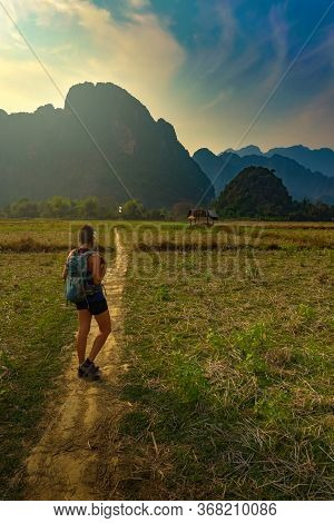 Backpacker Woman Walks Towards Towering Limestone Mountains Vang Vieng Laos