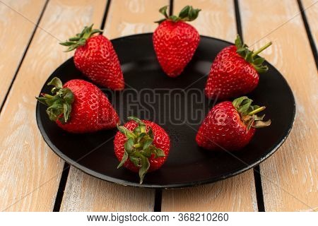 A Top View Red Strawberries Fresh Mellow Whole Inside Black Plate On The Wooden Floor