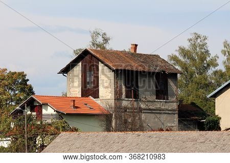 Abandoned Strange Looking Old Building With Destroyed Roof With Leaning Chimney And Broken Windows N