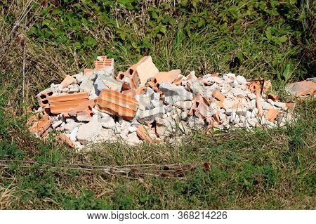 Pile Of Broken Bricks With Parts Of Concrete Building Blocks Mixed With Cracked Tiles And Other Cons