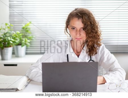 portrait of female doctor working on laptop telemedicine concept