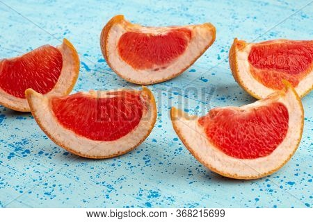 A Top View Sliced Grapefruits Juicy Mellow On The Bright Blue Background