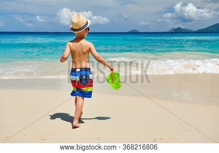 Three year old toddler boy playing with beach toys on beach. Summer family vacation at Seychelles, Mahe.