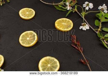 A Top View Lemon Sliced Sour Mellow Juicy Around White Flowers On The Dark Background