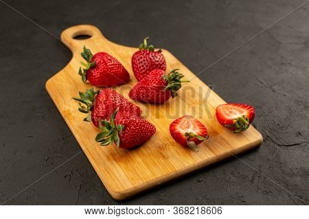 A Front View Strawberries Red Sliced And Whole Mellow Juicy On The Dark Floor