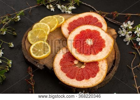 A Top View Sliced Citrus Fruits Grapefruits And Lemons Mellow Ripe On The Brown Desk And Dark Backgr
