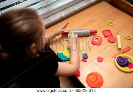 Close Up Of Child Playing With Play Dough In A Playroom On A Wood Table. Girl Molding Modeling Clay.