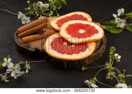 A Top View Sliced Grapefruit Fresh Mellow Juicy Along With Cinnamon On The Dark Floor
