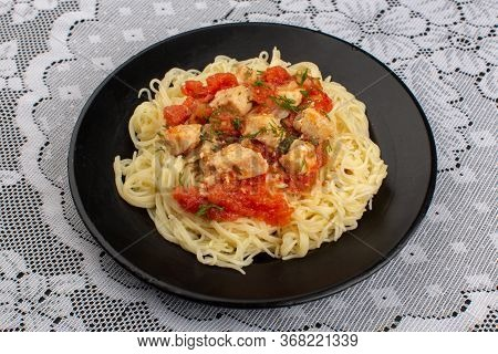 A Top View Pasta Cooked Tasty With Chicken Wings Cooked And Tomatoe Sauce Inside Black Palte On The