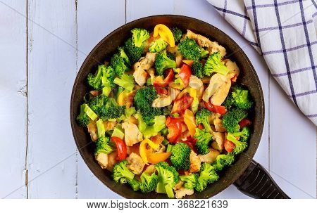 Healthy Stir Fry Vegetables With Chicken In Pan On White Wooden Surface.