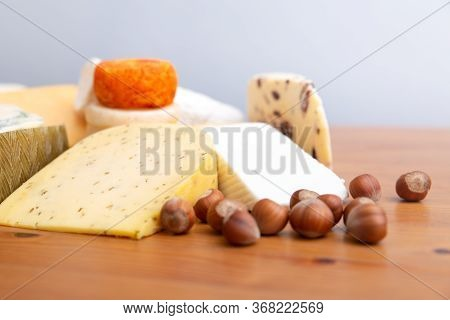 Cheese Slices And Macadamia Nuts On Wooden Table. Closeup Shot. Delicatessen Or Restaurant Cuisine C