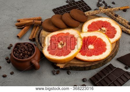 A Front View Sliced Citrus Mellow Ripe Grapefruit Along With Choco Cookies And Cinnamon On The Grey