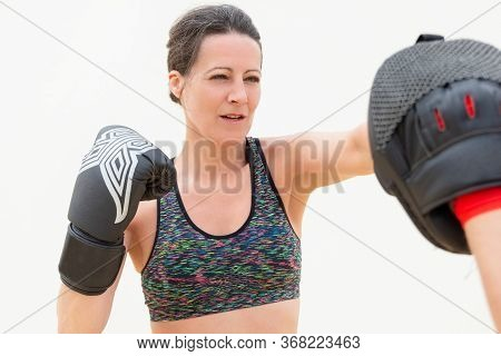 Concentrated Woman Punching Boxing Paw. Middle-aged Lady In Sport Bra Training Punch In Boxing Glove