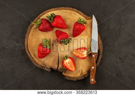 A Top View Fresh Red Strawberries Sliced Mellow Ripe On The Brown Desk And Dark Background