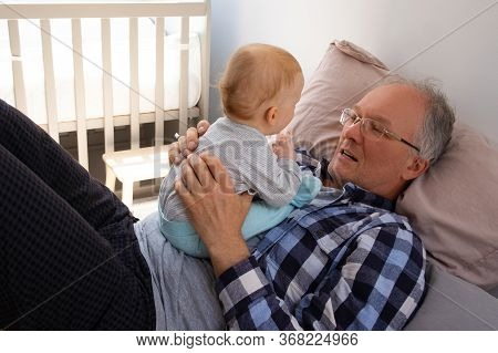 Little Red-haired Baby Sitting On Grandpa Belly. Senior Man Laying On Bed And Talking With Cute Todd
