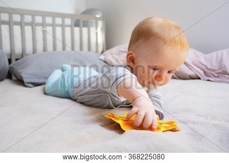 Pensive Little Child Playing With Mirror And Laying On Blanket. Cute Red-haired Toddler Surrounded P
