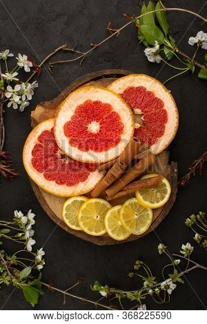 A Top View Fresh Citruses Sliced Mellow Along With Cinnamon On The Dark Background