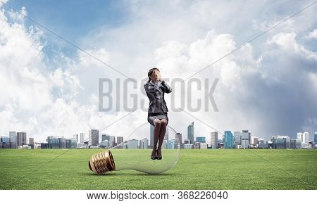 Young Woman Sitting On Big Light Bulb. Girl In Business Suit Keeps Hands On Face For Surprise. Busin