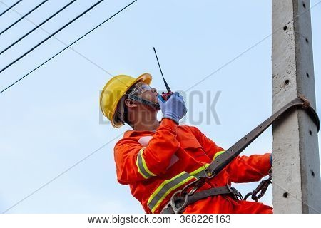 Uniformed Electricians Work On High-rise Electricity Poles Along With Safety Equipment And Using Rad