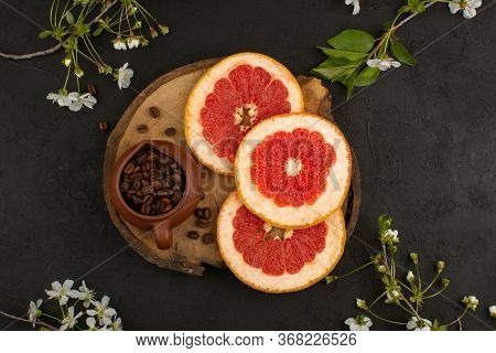 A Top View Sliced Grapefruit Fresh Mellow Juicy Along With Coffee Seeds On The Brown Desk On The Dar