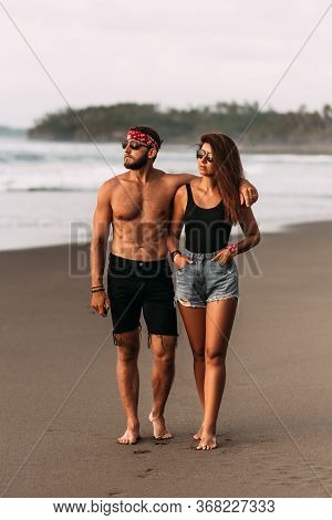 Happy Couple Strolling Along A Sandy Beach. Couple In Love At Sunset By The Sea. Vacation On The Isl