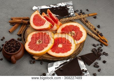A Top View Sliced Grapefruits Ring Fresh Mellow Juicy Along With Candy Sticks Choco Bars And Coffee