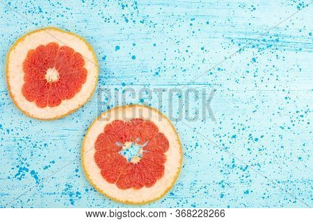 A Top View Grapefruit Sliced Rings Mellow Ripe On The Bright Blue Background