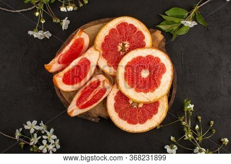 A Top View Sliced Grapefruits Fresh Mellow Juicy On The Brown Desk And Dark Background