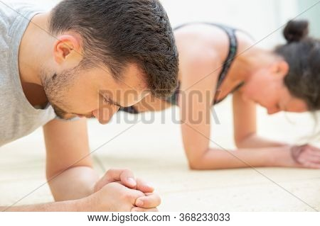 Concentrated Man And Woman Standing In Plank Pose. People Doing Exercise. Closeup View And Selective