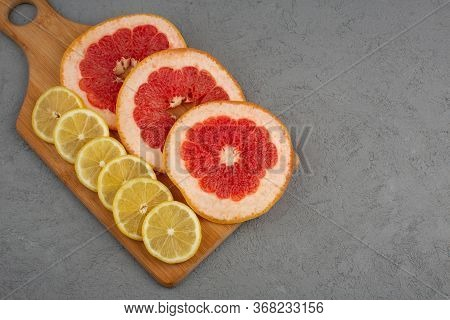 A Top View Sliced Citruses Fresh Mellow Juicy Grapefruits And Lemons On The Grey Floor