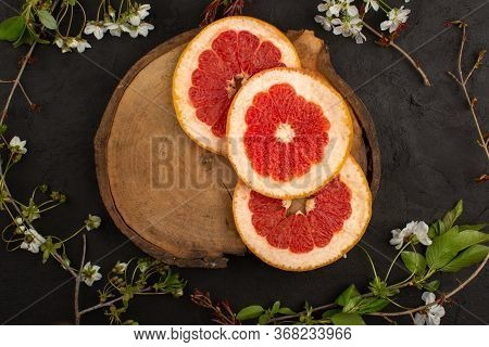 A Top View Sliced Grapefruit Juicy Ripe Mellow On The Dark Background