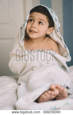 Selective Focus Of Happy Child, Wrapped In Hooded Towel, Looking Away While Sitting On Bed