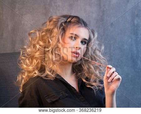 Portrait Of A Blonde Girl With Long And Volume Shiny Wavy Hair With Chewing Gum In Her Mouth. A Woma