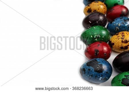Frame Of Multi-colored Quail Eggs. Multi-colored Quail Easter Eggs On A White Background. A Line Of