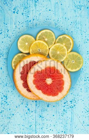 A Top View Citrus Slices Rings Juicy Mellow On The Bright Blue Background