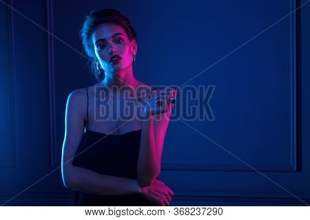 Frontal View Of A Woman With Bare Shoulders, Hairstyle And Makeup, Wear In Elegant Jewelry, Over Pur
