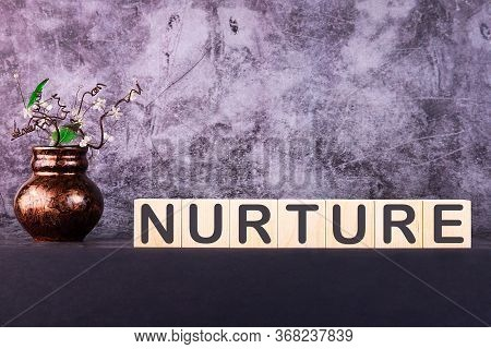 Word Nurture Made With Wood Building Blocks On A Gray Background.